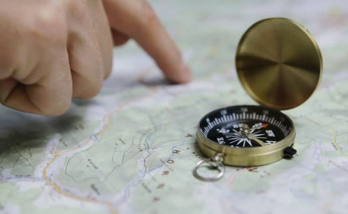 Men's finger planning hiking trip on a map with compass