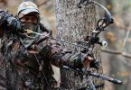 man with compound bow in the woods