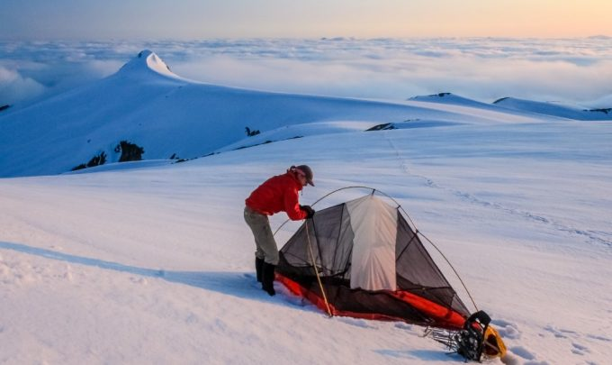 setting up a tent in the snow