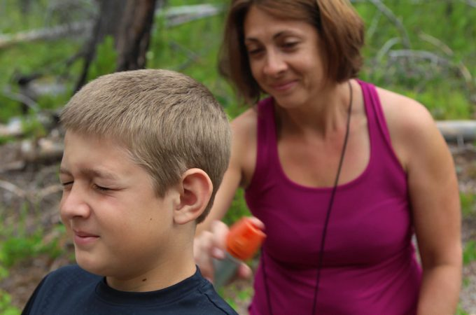 Woman applying insect repellent on a boy