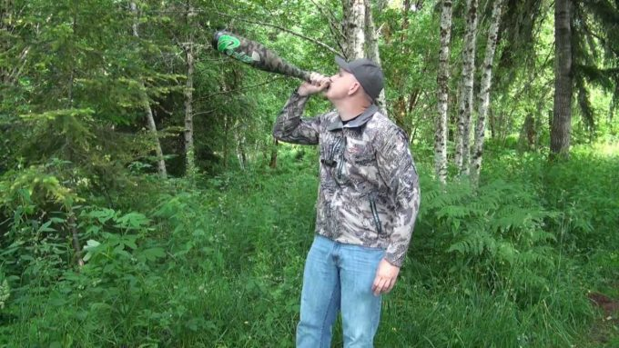 man using bugle tube elk call