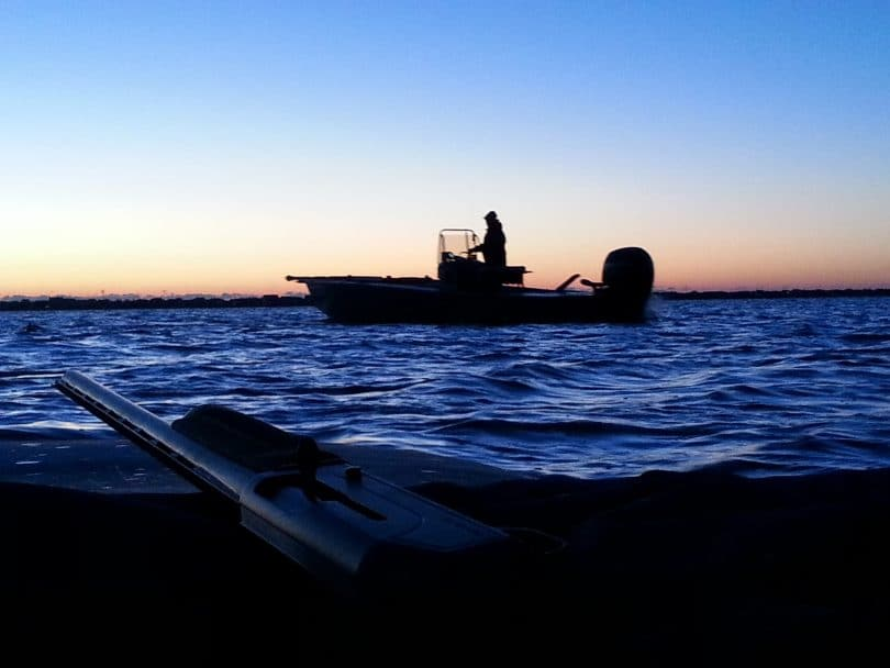 Boat at sunset with gun in foreground