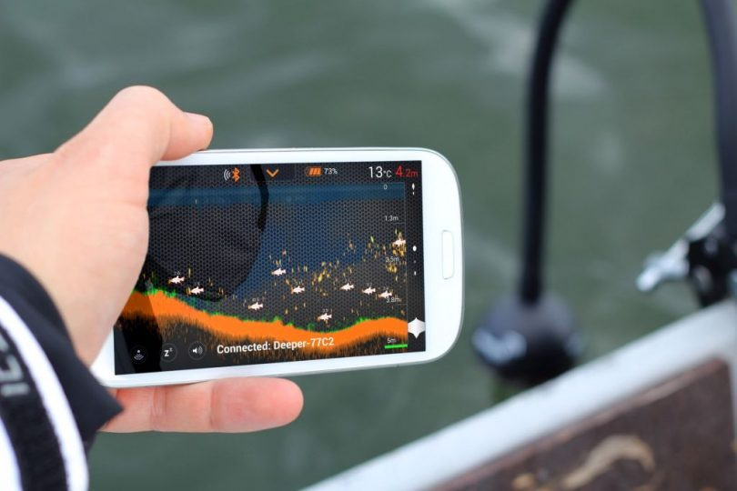hand holding phone with fish finder