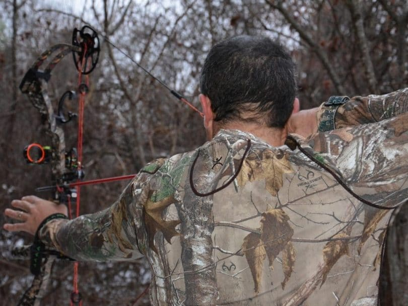Hunter holding a bow and wearing a base-layer