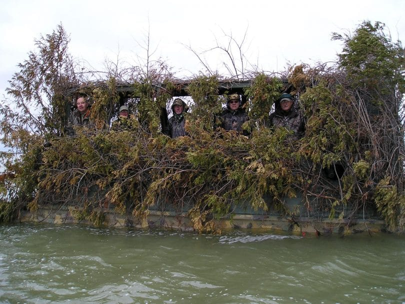 A canoe camouflage with hunters inside