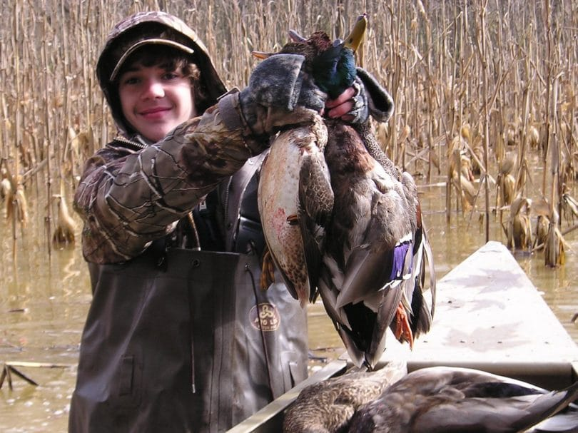 A kid showing off his duck kills