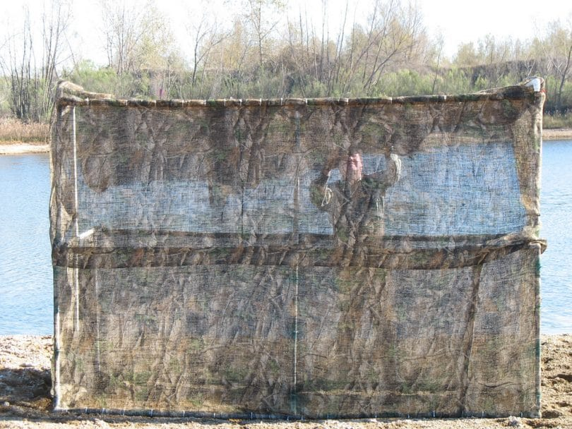 duck blind front view and man behind camo mesh
