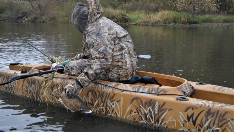 Hunter in a orange kayak with a fake duck