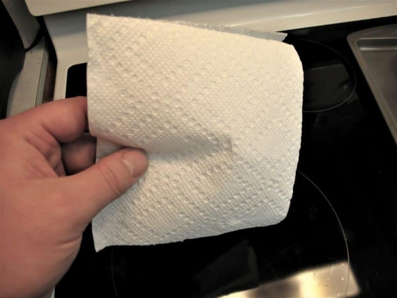 hand holding a sheet of toilet paper