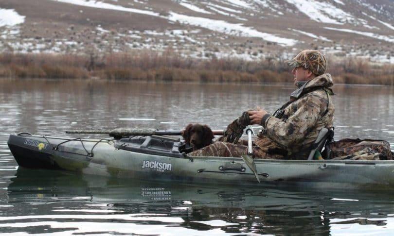 Hunter with dog in kayak