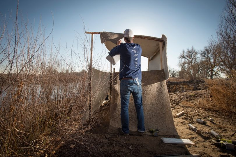 man bulding the side of a duck blind