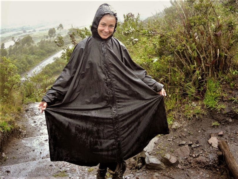 woman wearing a black gore tex poncho in the rain