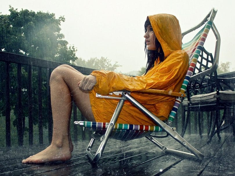women standing in a chair in the rain