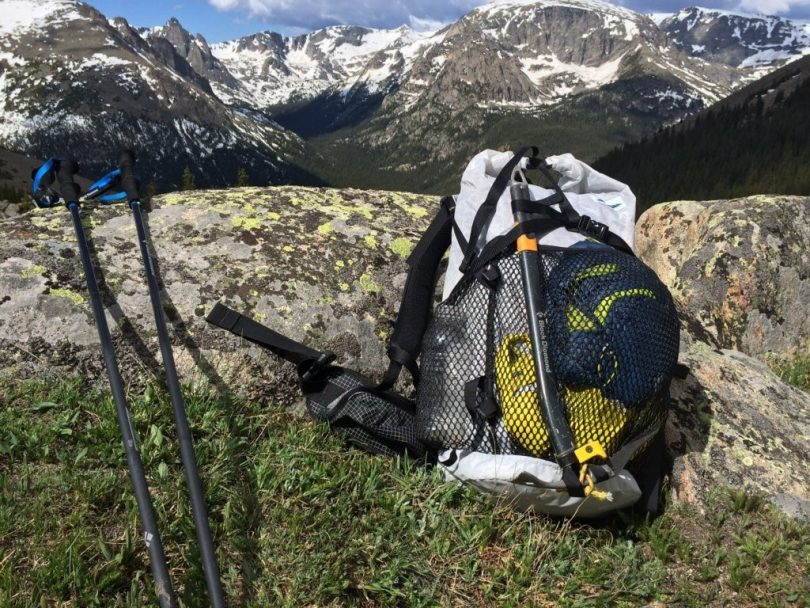 Backpack with ice axes and trekking poles in the mountains