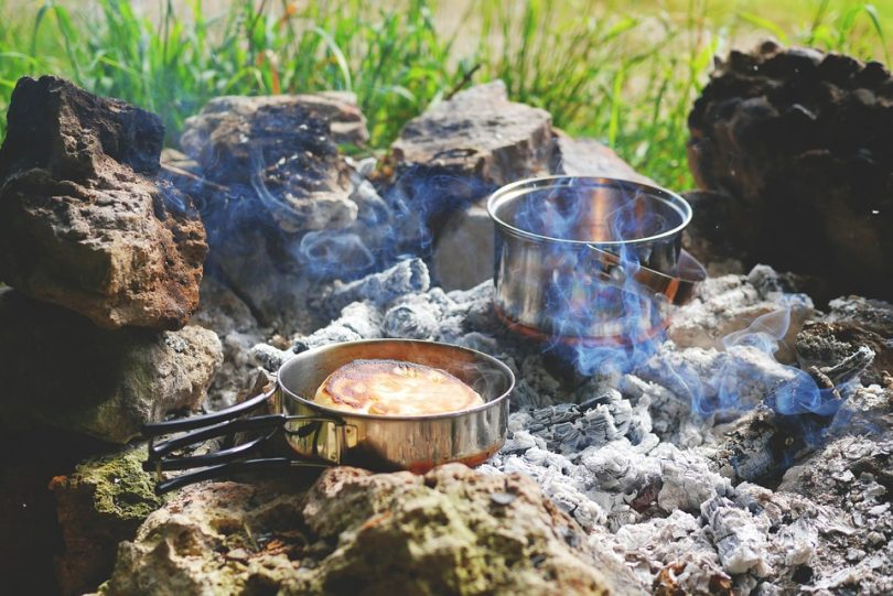 Cooking in metal pan on campfire