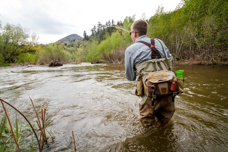Fly fisherman with backpack in river