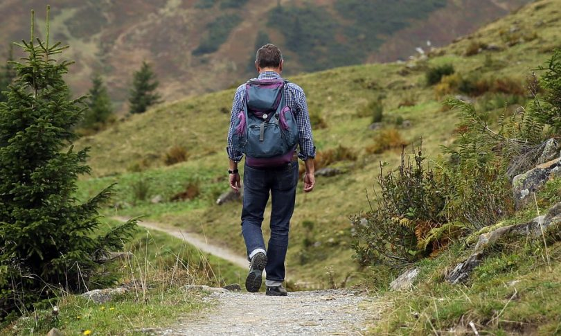 Man with backpack hiking in natural landscape