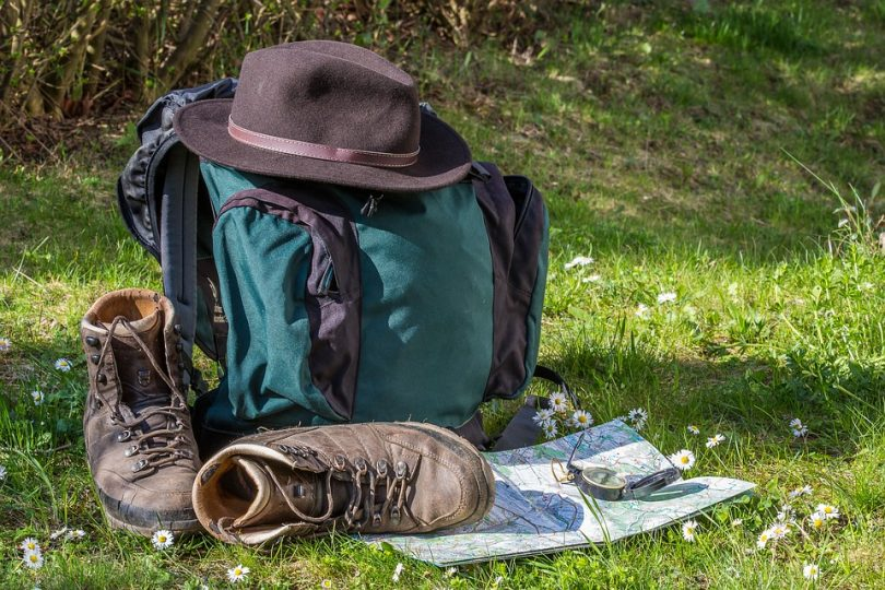 Rucksack with old boots, map, compass and hat on the grass