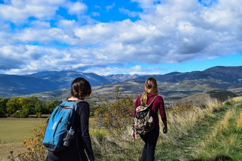 Two girls with backpacks walking