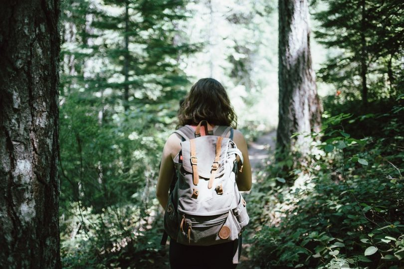 Woman with a backpack walking in forest