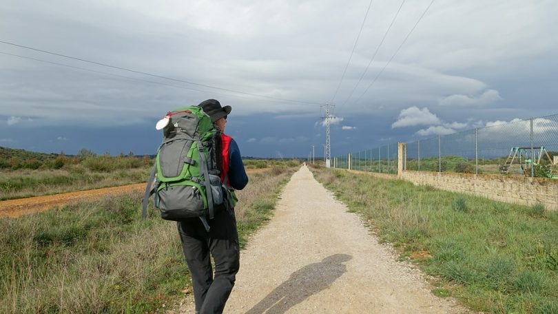 Woman with backpack walking on rural path