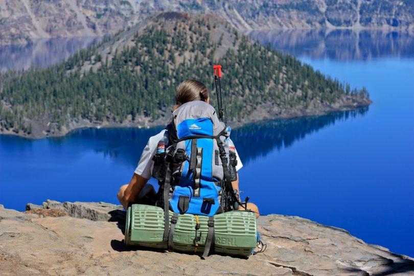 Girl backpacker is sitting on rock peak over lake