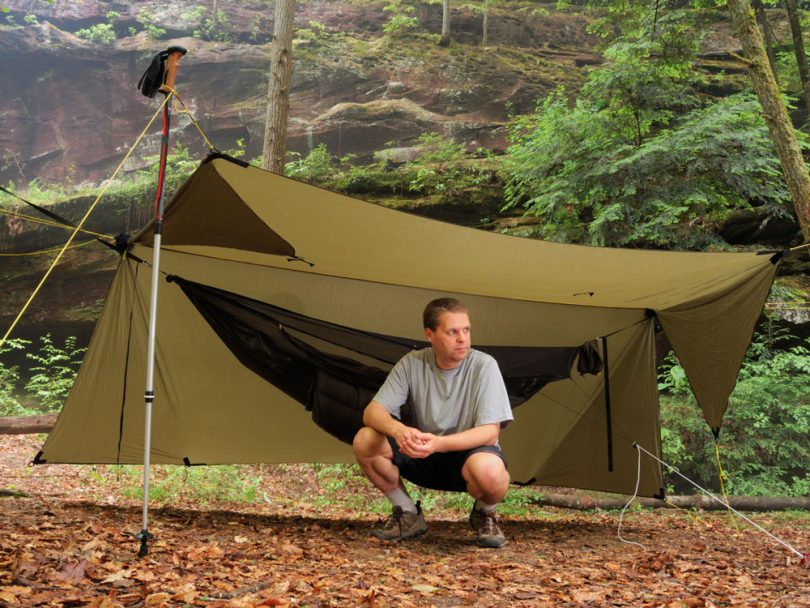 Man near modern camping hammock under tarp