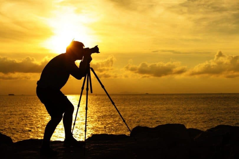 Silhouette of photographer with tripot at sunset