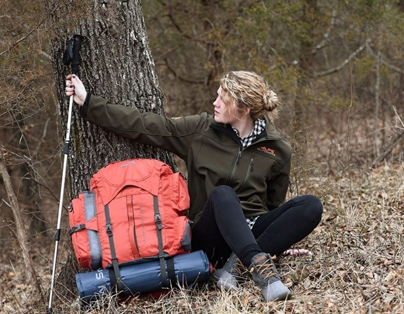 Woman hiker with external backpack sitting near tree