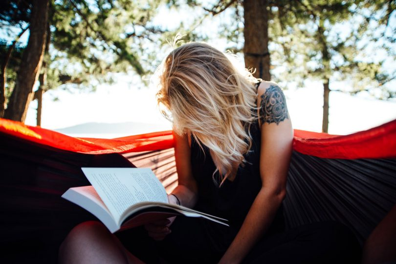 Woman reading hiking and adventure book