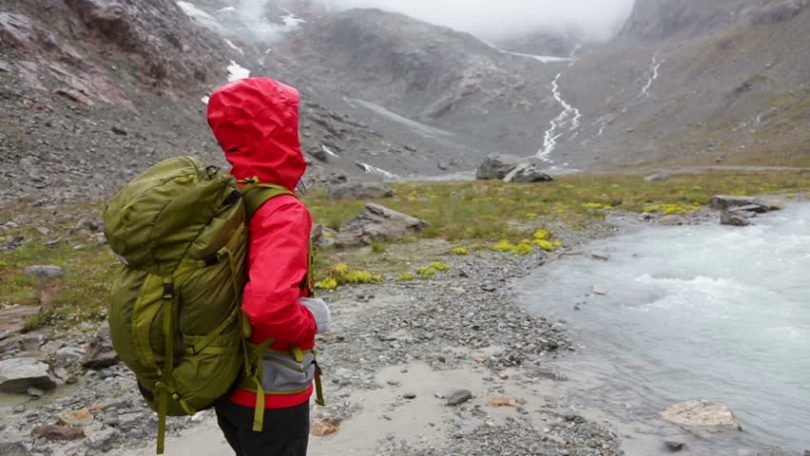 Woman walking by river in mountain during rainy season