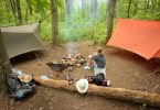 Young girl resting by campfire in wooded campsite