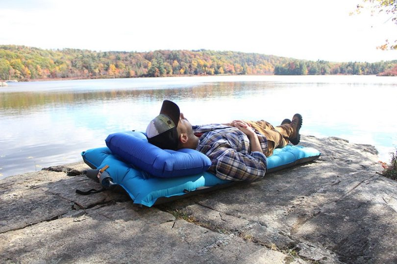 Young man lying on camping bed near lake