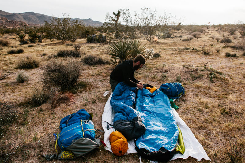 Backpacker unpacking his sleeping gear