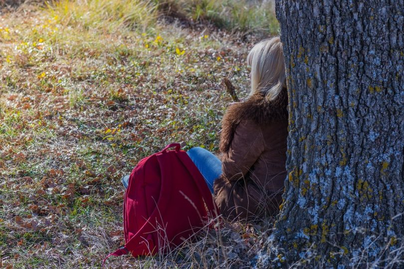 Hiker woman rests near tree