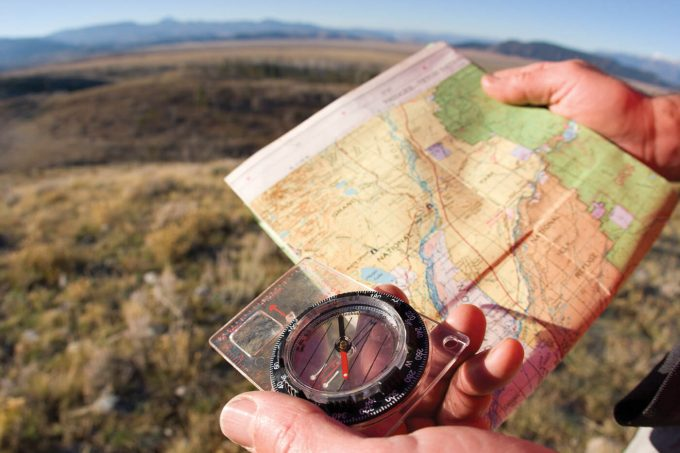 Compass and map in the hands of man