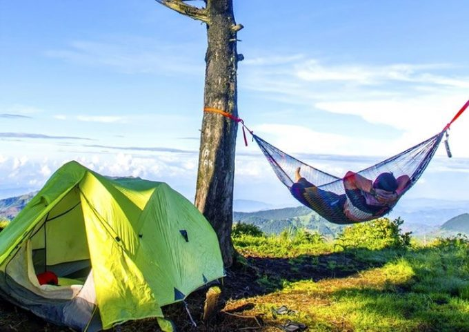 Man lying hammock beside camping tent