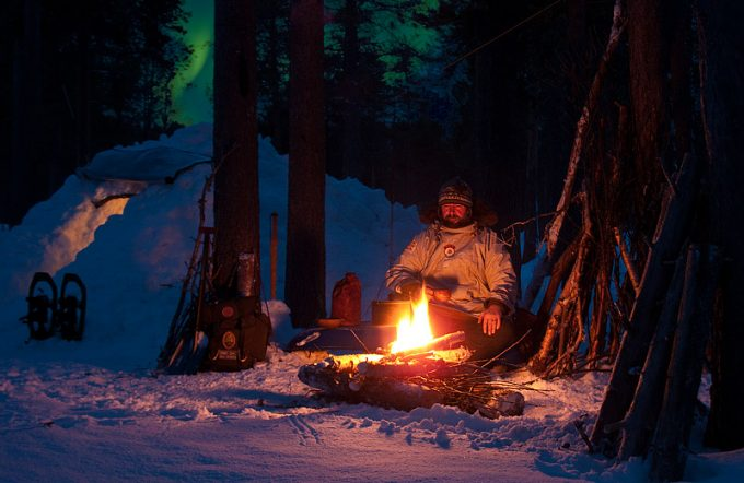 Man sitting on log near campfire in the camping