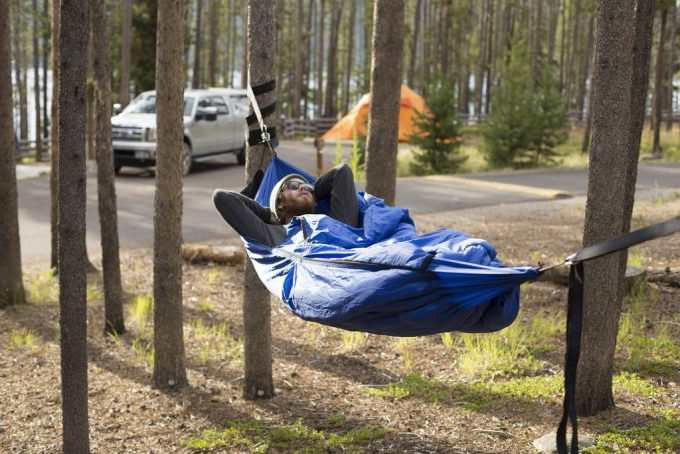 Man sleeps in a hammock and in a sleeping bag