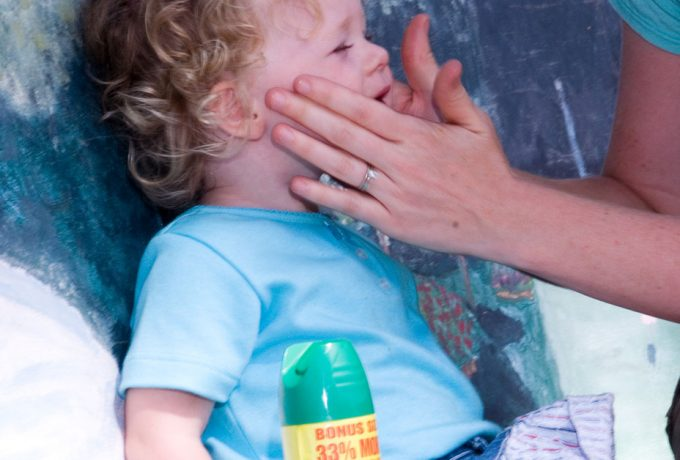 Mother putting insect repellent on toddler
