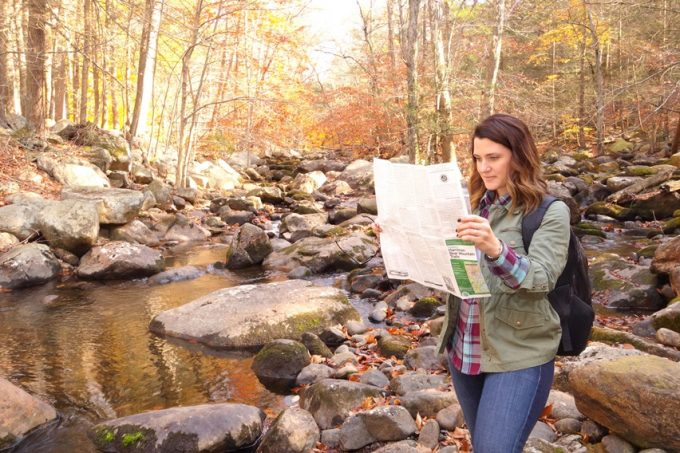 Woman hiker in the forest read the map