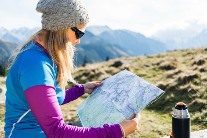 Woman hiker reading and checking map