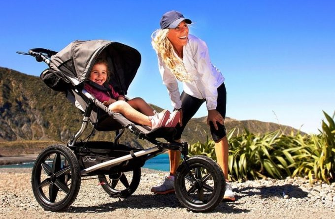 Woman jogging with baby in a jogging stroller