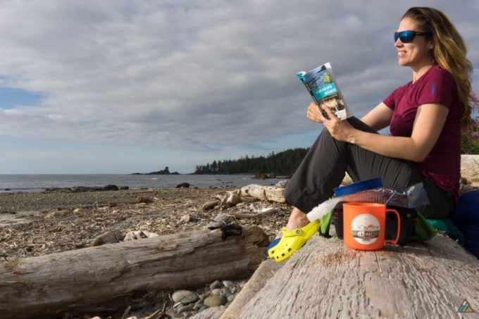 Young woman hiker reading book