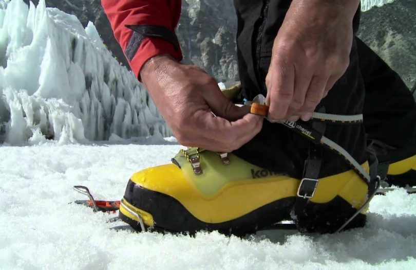 man adjusting his mountaineering boots