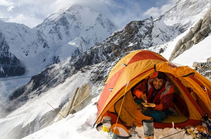 man eating in a mountaineering tent
