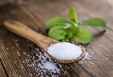 sugar in a wooden spoon and herb