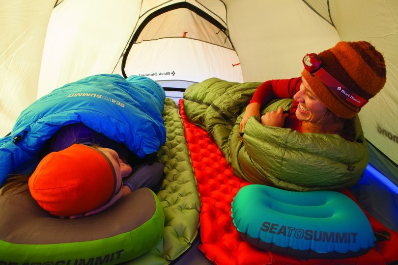 two people laying in a tent