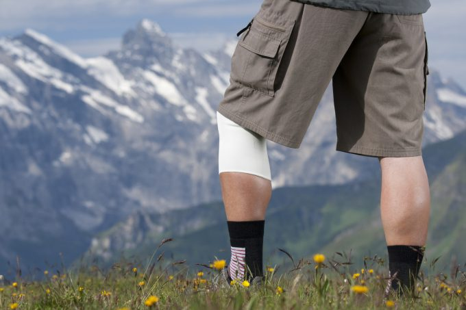 Elderly hiker with bandage on knee