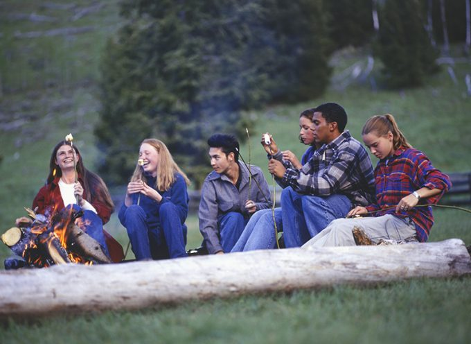 Group of teenagers in country field eating marshmallows by campfire